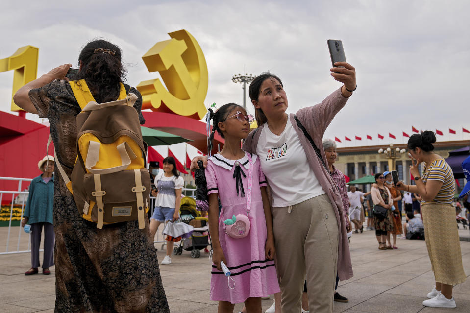 Visitors take souvenir photos with a communist party's logo on display at Tiananmen Square to mark the 100th anniversary of the founding of the ruling Chinese Communist Party in Beijing on Monday, July 5, 2021. Chinese leader Xi Jinping on Tuesday attacked calls from some in the U.S. and its allies to limit their dependency on Chinese suppliers and block the sharing of technologies. (AP Photo/Andy Wong)