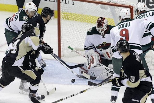 Pittsburgh Penguins' Pascal Dupuis (9) gets to a rebound off Minnesota Wild goalie Niklas Backstrom (32) and gets it past Backstrom for a goal in the first period of an NHL hockey game in Pittsburgh, Thursday, Dec. 19, 2013. (AP Photo/Gene J. Puskar)