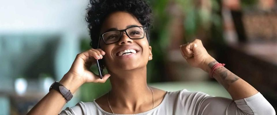 Happy black businesswoman laughing with joy, on the telephone