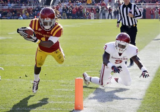 Iowa State wide receiver Jarvis West, left, dives to the end zone ahead of Oklahoma defensive back Gabe Lynn, right, during a 19-yard touchdown run in the second half of an NCAA college football game, Saturday, Nov. 3, 2012, in Ames, Iowa. Oklahoma won 35-20. (AP Photo/Charlie Neibergall)