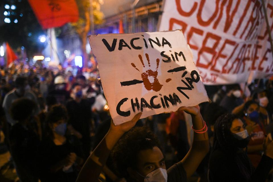 A man holds a sign written in Portuguese '' Vaccine yes, slaughter no. '' during a  protest against racism and police violence amidst the Coronavirus (COVID-19) pandemic in Rio de Janeiro, Brazil, on May 13, 2021.A massive police operation against drug traffickers in Jacarezinho favela left 25 people dead on Thursday May 6, while residents and activists claimed human rights abuses. (Photo by Andre Borges/NurPhoto via Getty Images)