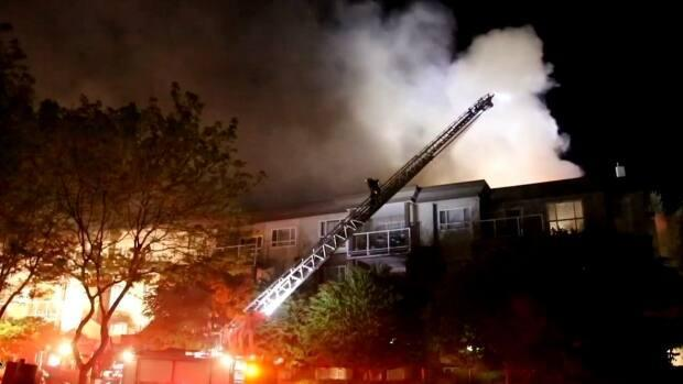 Firefighters in Surrey, B.C., battled for hours against a fire at a four-storey building in the Fleetwood neighbourhood that displaced dozens of households.  (Shane MacKichan - image credit)