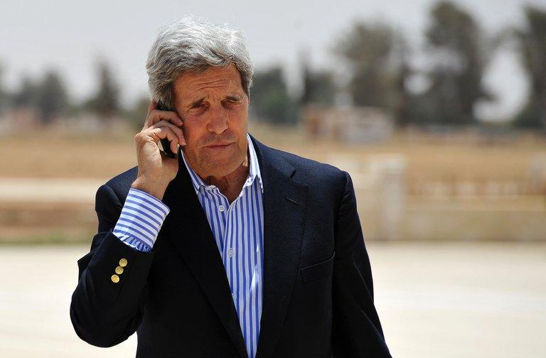 US Secretary of State John Kerry speaks on the phone at Mafraq air base before boarding a helicopter to Amman, after visiting Zaatari refugee camp in Jordan on July 18, 2013. Kerry Friday met with chief Palestinian negotiator Saeb Erakat in a final push to get a peace bid back on track before heading home