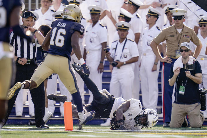 UCF wide receiver Brandon Johnson, right, dives for a touchdown after making a catch against Navy cornerback Jamal Glenn (16) during the first half of an NCAA college football game, Saturday, Oct. 2, 2021, in Annapolis, Md. (AP Photo/Julio Cortez)