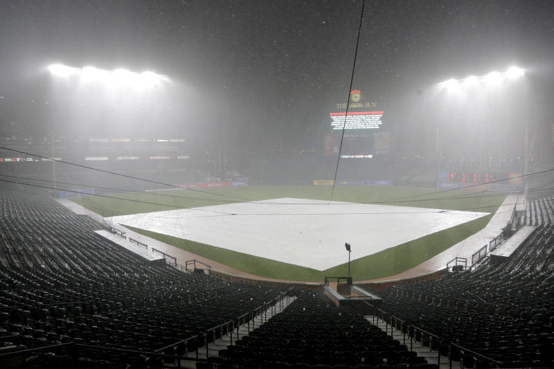 Rain pours down during a delay during the fifth inning of a baseball game between the Baltimore Orioles and the Tampa Bay Rays, Thursday, Aug. 22, 2019, in Baltimore. (AP Photo/Julio Cortez)