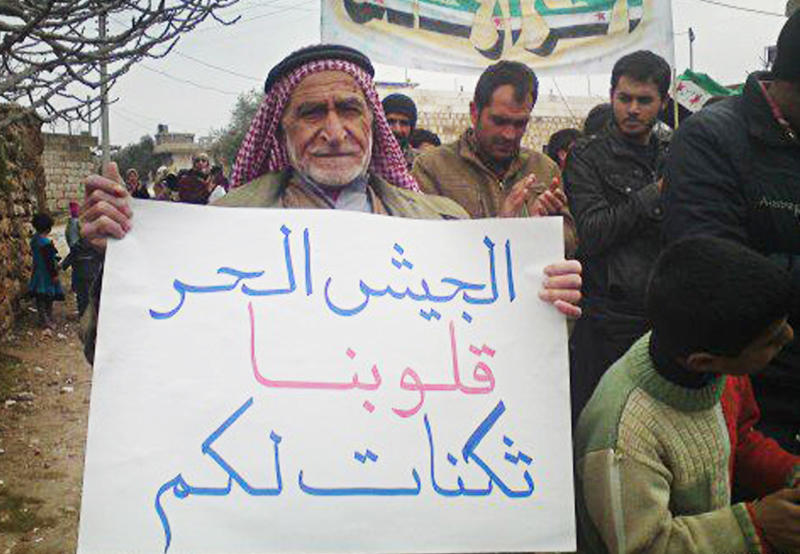 "In this citizen journalism image provided by the Local Coordination Committees in Syria and released Wednesday, Feb. 1, 2012, an anti-Syrian regime protester, holds a poster in Arabic that reads, ""to the Syrian freedom soldiers, our hearts are bases for you,"" as he walks during a demonstration in Idlib Province, north Syria. Russia's deputy defense minister says Moscow will not stop arms sales to Syria. Russian state news agencies quoted Deputy Defense Minister Anatoly Antonov on Thursday as saying Russia is not violating any international obligations. (AP Photo/Local Coordination Committees in Syria)  THE ASSOCIATED PRESS IS UNABLE TO INDEPENDENTLY VERIFY THE AUTHENTICITY, CONTENT, LOCATION OR DATE OF THIS HANDOUT PHOTO"