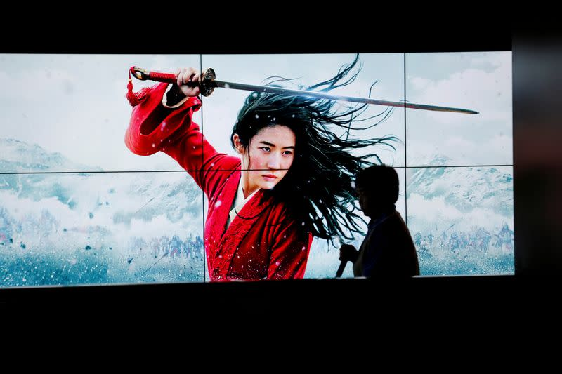 """FILE PHOTO: Cleaner walks past screens promoting Disney's movie """"Mulan"""" as the film opens in China, at a cinema in Beijing"""