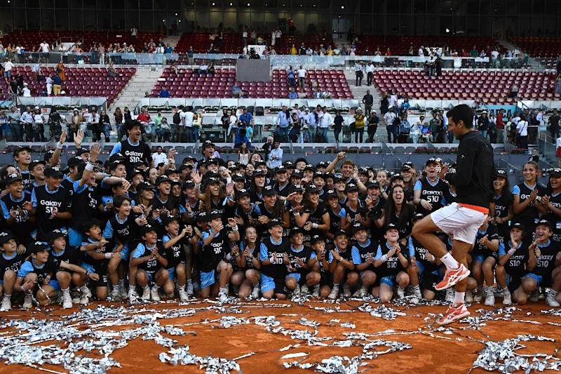 Novak Djokovic holds his trophy as he celebrates  after winning the Madrid Open