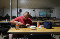 Josh Anderson, Minneapolis, Minn., an electrical worker for Sparks Energy, eats a dinner in a cafeteria of a tent city for electrical workers, in Amelia, La., Thursday, Sept. 16, 2021. In one massive white tent, hundreds of cots are spread out; experienced workers bring their own inflatable mattresses. Another tent houses a cafeteria that serves hot breakfast starting about 5 a.m., dinner and boxed lunches that can be eaten out in the field. (AP Photo/Gerald Herbert)
