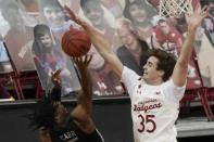 Wisconsin's Nate Reuvers blocks the shot of Minnesota's Marcus Carr during the second half of an NCAA college basketball game Thursday, Dec. 31, 2020, in Madison, Wis. (AP Photo/Morry Gash)