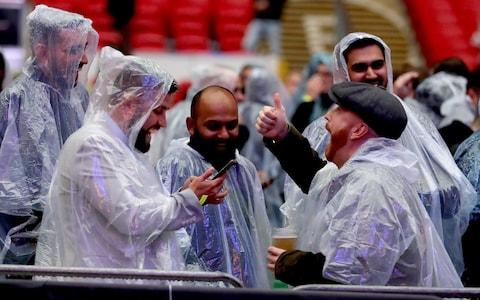 Fans enjoy the pre fight atmosphere in the stands while wearing rain coats at Wembley Stadium - Credit: Richard Heathcote/Getty Images