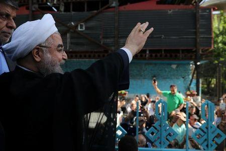 Iran's President Hassan Rouhani waves to supporters at a polling station during the presidential election in Tehran