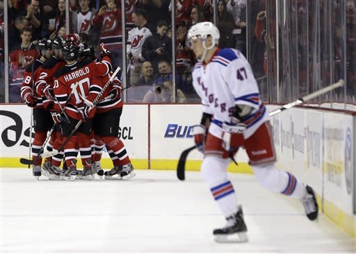New York Rangers center J.T. Miller (47) walk out of the penalty box as members of the New Jersey Devils celebrate a goal by Travis Zajac during the first period of an NHL hockey game, Tuesday, March 19, 2013, in Newark, N.J. (AP Photo/Julio Cortez)