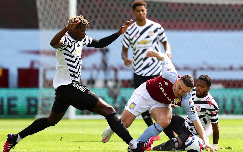 John McGinn of Aston Villa battles for possession with Paul Pogba of Manchester United - Getty