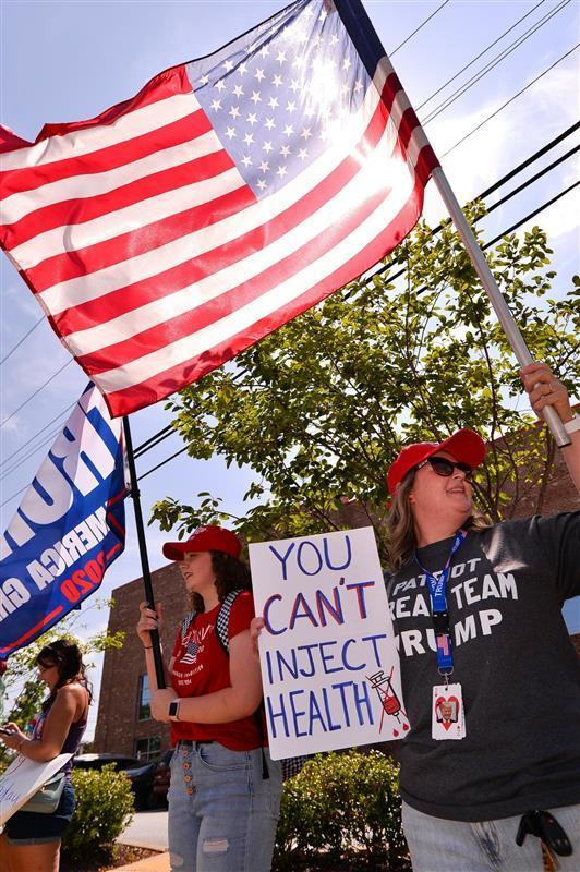 Trump supporters with the MYSCGOP group, including Nicole Morgan, right, and her daughter McKenna Morgan, left, protest as Vice President Kamala Harris visits Greenville Monday morning.