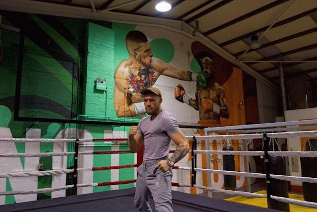 Conor McGregor poses in front of a mural showing him boxing Floyd Mayweather. (Courtesy photo)