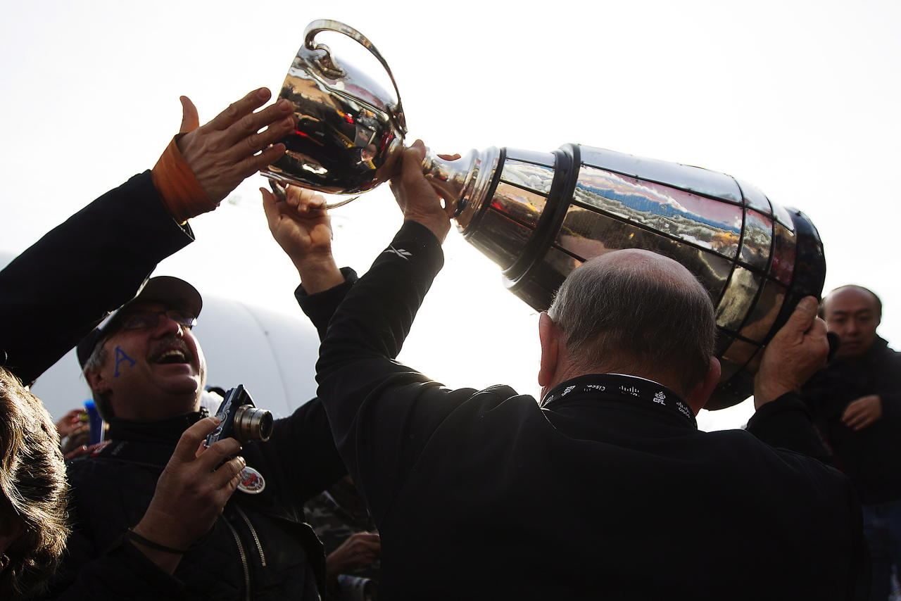 Fans reach out and touch the Grey Cup as Ottawa Rough Riders alumni Russell Jackson hoists it above his head to kick off the fan march before the Toronto Argonauts take on the Calgary Stampeders for the 100th Grey Cup in Toronto on Sunday, Nov. 25, 2012. THE CANADIAN PRESS/Michelle Siu