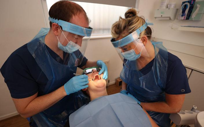 Dentists wearing personal protective equipment - Liam McBurney/PA