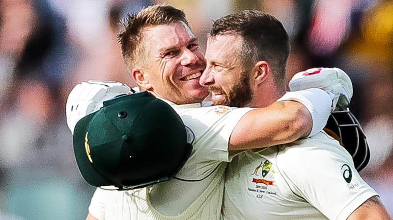 David Warner, pictured left, embraces Matthew Wade during day two of Australia's test against Pakistan in Adelaide.