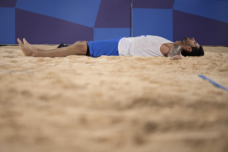 Viacheslav Krasilnikov, of the Russian Olympic Committee, lays on the sand after winning a men's beach volleyball semifinal match against Qatar at the 2020 Summer Olympics, Thursday, Aug. 5, 2021, in Tokyo, Japan. (AP Photo/Felipe Dana)