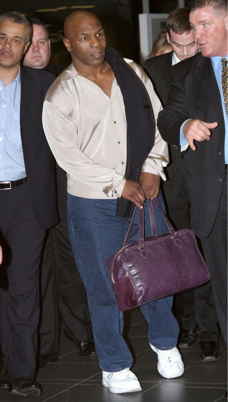 <p>Mike Tyson travels in style in a silk button-down shirt and leather carry-on, as he arrives in Dublin, Ireland in March 2006. </p>