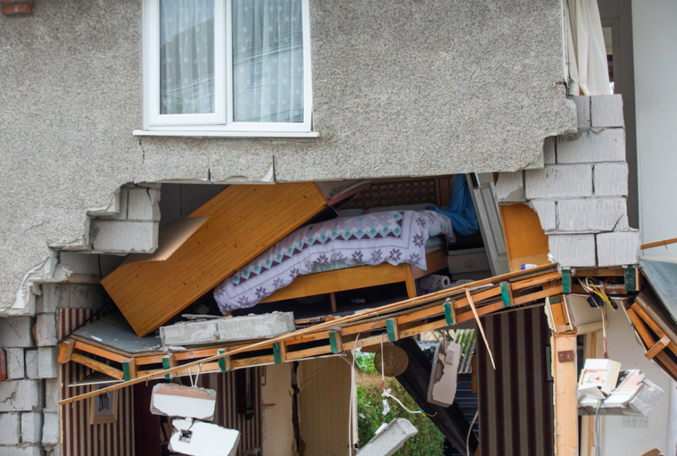 A double bed is exposed to the street from an upper floor room hanging precariously after the support collapsed below. (SWNS)