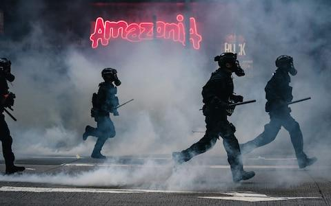 Riot police fire multiple tear gas and pushing forward in front of the Amazonia Bar at Wan Chai district - Credit: Getty