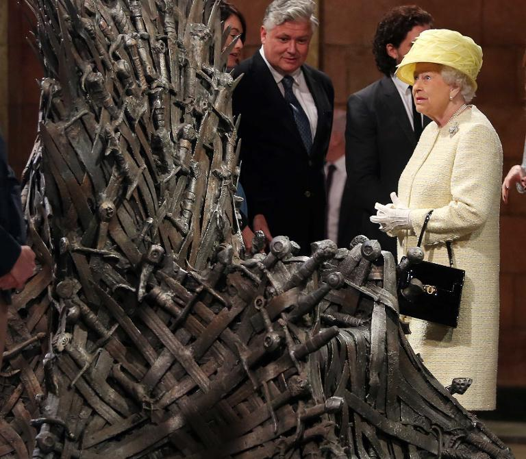 """Queen Elizabeth II views props during her visit to the set of the HBO TV series """"Game of Thrones"""" in the Titanic Quarter in Belfast on June 24, 2014"""