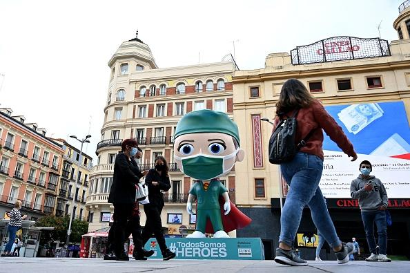 """People wearing face masks walk on by a six metre statue depicting a """"Superhealthworker"""" installed in Madrid to pay tribute to the heroes who fight against coronavirus."""