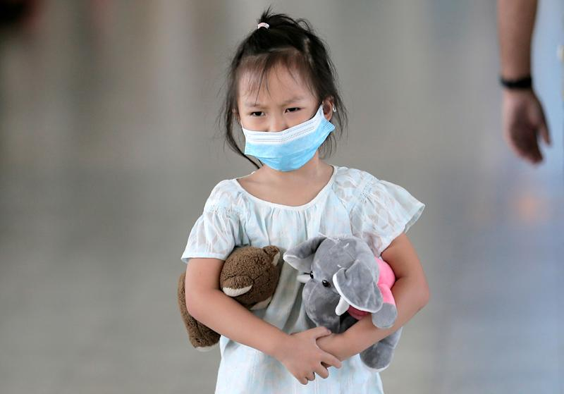 A girl wears a mask as she walks past a scanning machine monitoring people's temperature following the new coronavirus outbreak from China, at Bandaranaike international airport in Katunayake, Sri Lanka January 24, 2020. REUTERS/Dinuka Liyanawatte