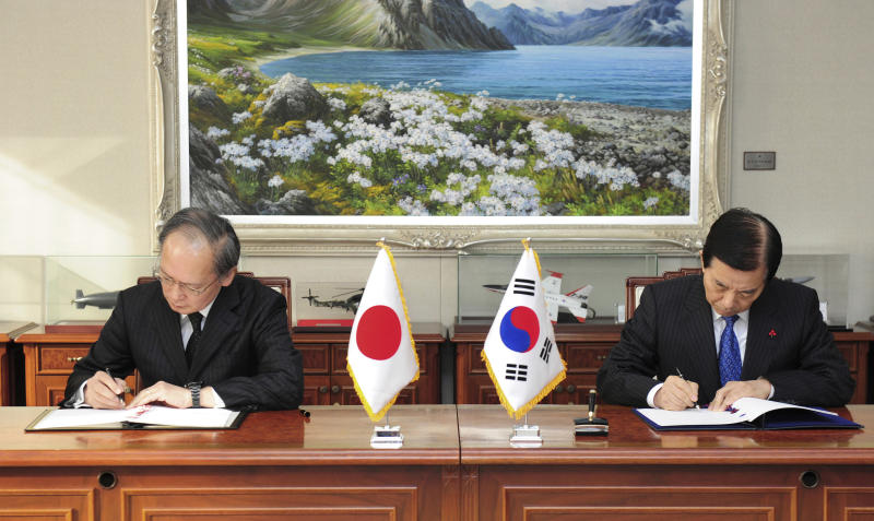 FILE - In this Nov. 23, 2016, file photo provided by South Korean Defense Ministry, South Korean Defense Minister Han Min Koo, right, and Japanese Ambassador to South Korea Yasumasa Nagamine sign the General Security of Military Information Agreement, or GSOMIA, an intelligence-sharing agreement between South Korea and Japan in Seoul, South Korea. South Korea has threatened to end the military intelligence sharing agreement with Japan as their tensions escalate over export controls. The agreement, known as GSOMIA, is a symbol of the countries' trilateral security cooperation with their ally United States in the region. (South Korean Defense Ministry via AP, File)