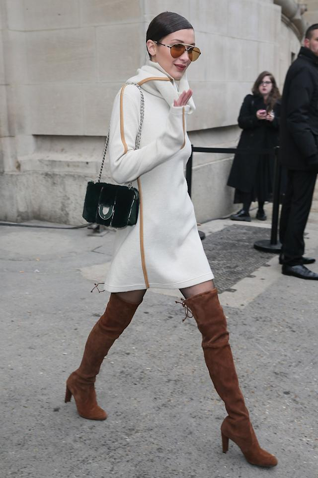 <p>Bella showed her street style prowess in a luxe knit, tinted sunglasses and suede thigh-high boots. <i>[Photo: Getty]</i> </p>