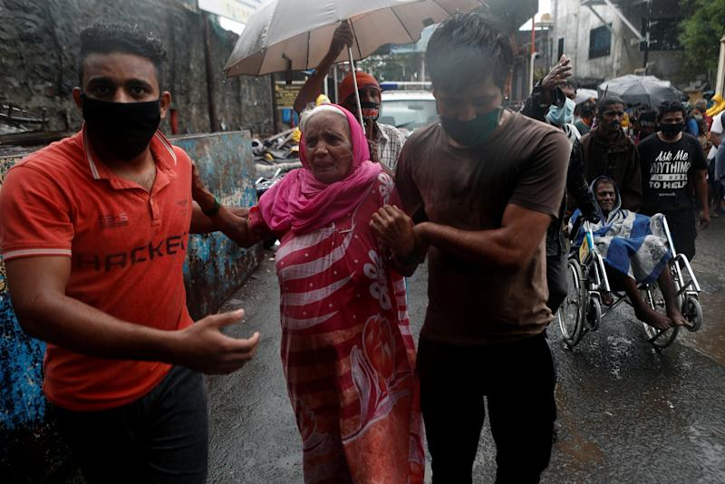 People help elderly citizens during an evacuation from a Mumbai slum: REUTERS