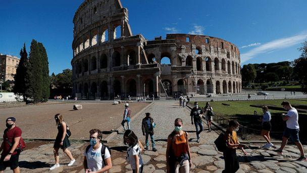 PHOTO:People wear protective face masks walk past the Colosseum as local authorities in the Italian capital Rome ordered face coverings to be worn at all times outdoors, in an effort to counter the spread of the coronavirus disease in Rome, Oct. 8, 2020. (Guglielmo Mangiapane/Reuters)