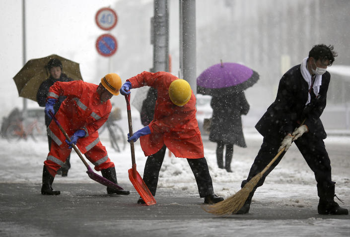 Railway station workers shove snow from the street in Yokohama, Japan, Saturday, Feb. 8, 2014. The Japan Meteorological Agency issued the first heavy snowfall warning for central Tokyo in 13 years. Some 20-centimeter (7.9-inch) of snowfall is expected by Sunday morning in the metropolitan areas. (AP Photo/Eugene Hoshiko)