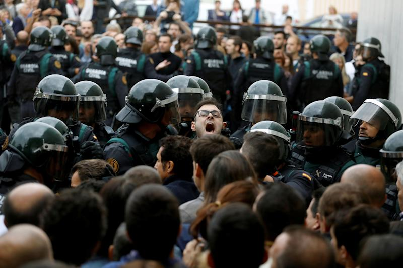 Scuffles break out as Spanish Civil Guard officers force their way through a crowd and into a polling station.