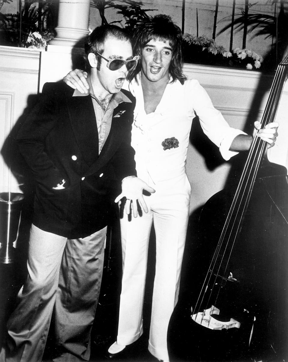 CIRCA 1976: Pop singers Rod Stewart and Elton John pal around at an event in circa 1976. (Photo by Michael Ochs Archives/Getty Images)