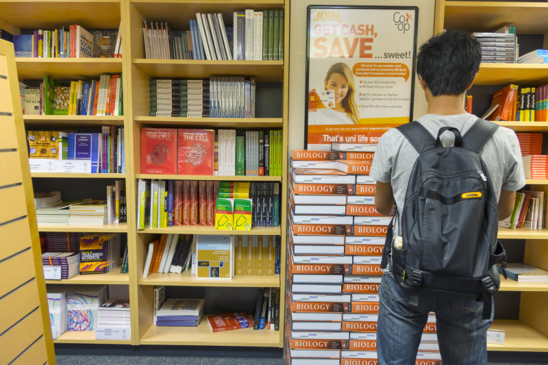 A student stands in from of books in a campus bookstore.