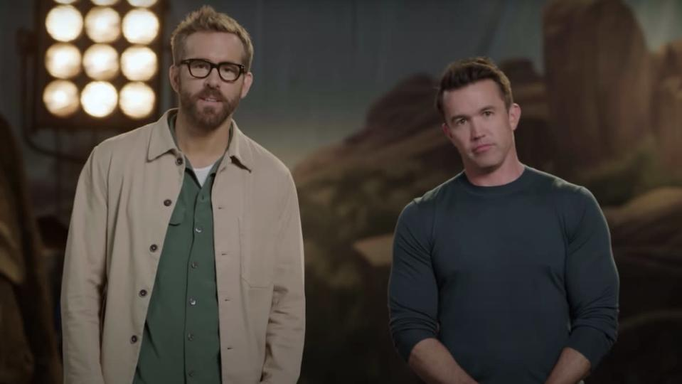 Ryan Renyolds with a beard and glasses in a green shirt and brown coat next to a clean shaven Rob McElhenney in a dark shirt