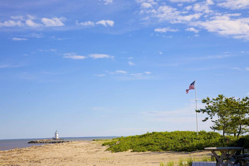 <p>A sand dune and lighthouse in the background of the beach at Old Saybrook, one of the oldest towns in the state.</p>