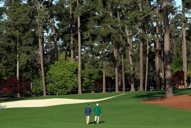 An Augusta National member walks with a patron during the first day of practice for the 2018 Masters golf tournament at Augusta National Golf Club in Augusta, Georgia, U.S. April 2, 2018. REUTERS/Mike Segar