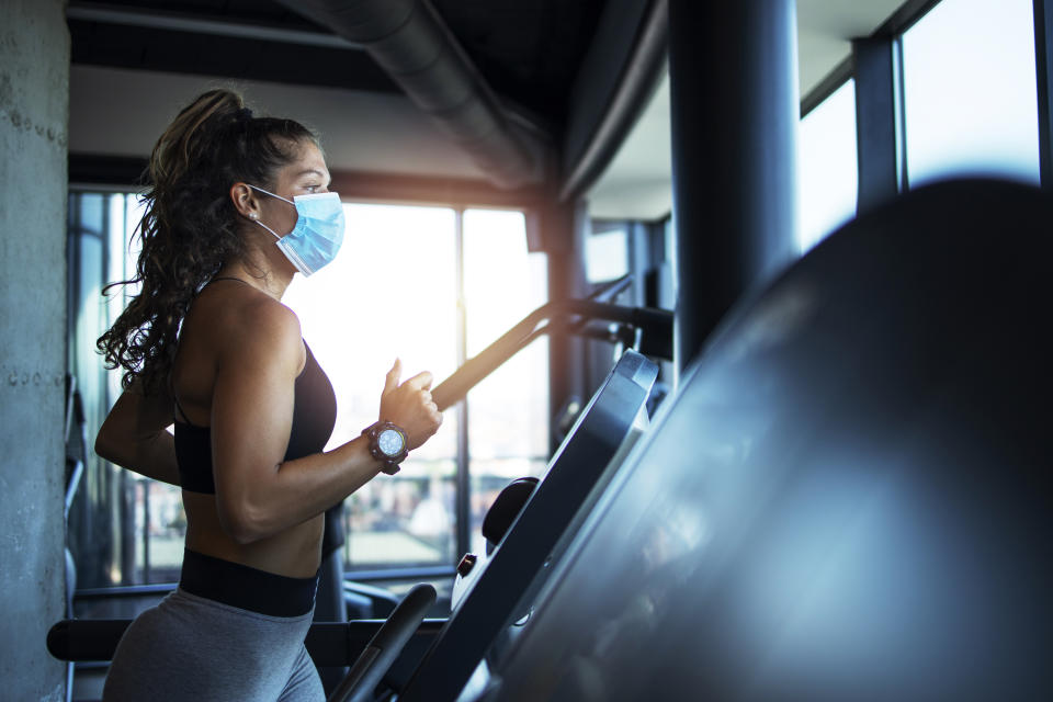 Sportswoman training on treadmill in gym and wearing face mask to protect herself against coronavirus during global pandemic of covid-19 virus.