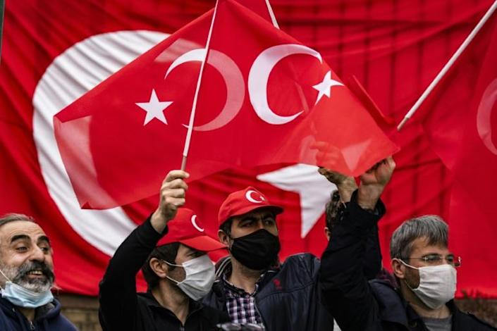Turkish counter-protestors wave flags in Washington hours after President Biden recognized the Armenian genocide