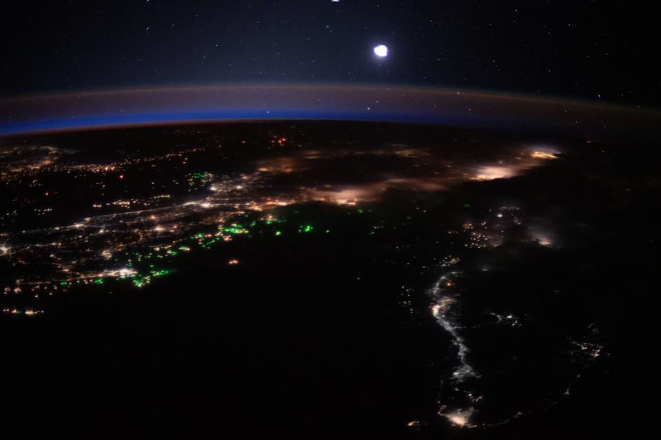 City lights of Malaysia and Indonesia light up the Earth beneath a blanket of blue and orange airglow while boat lights glow in the Bay of Bengal in this nighttime view of Earth from space. An Expedition 62 astronaut captured this photo from the International Space Station on March 21, when the space station was orbiting 262 miles (422 kilometers) overhead.