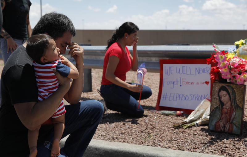 Dr. Julio Novoa, left, and Danielle Novoa, right, kneel beside a makeshift memorial with their 10-month-old son Ricard Novoa at the scene of a mass shooting at a shopping complex Sunday, Aug. 4, 2019, in El Paso, Texas. (AP Photo/John Locher)