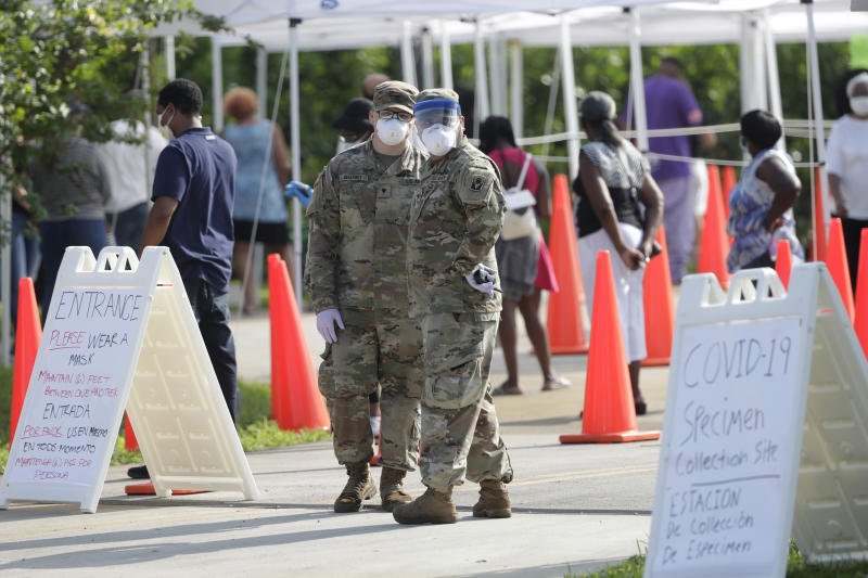 National Guardsmen look on as people wait in line at a walk-up coronavirus testing site during the COVID-19 pandemic, Saturday, April 18, 2020, at the Urban League of Broward County in Fort Lauderdale, Fla. (AP Photo/Wilfredo Lee)