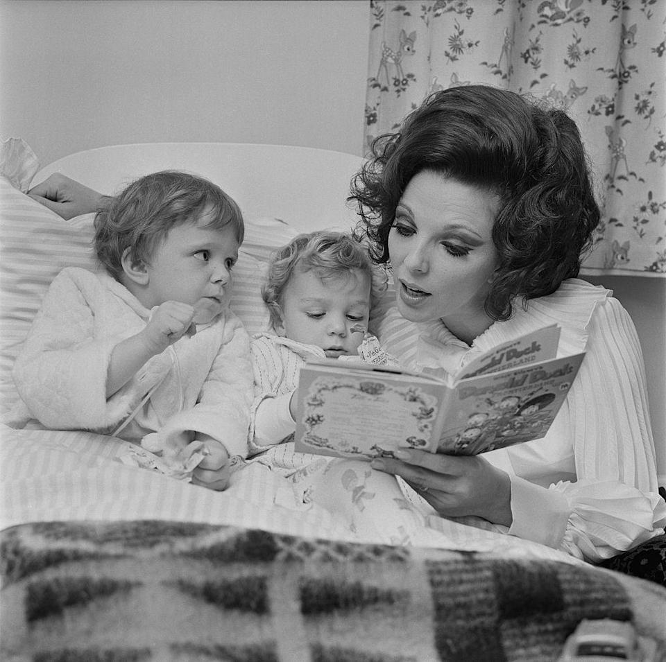 <p>After tucking her children into bed, Joan reads them a Donald Duck book in 1967. The actress was at the time married to singer Anthony Newley. </p>