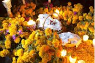 "<p>Another important Day of the Dead symbol is the marigold. These bright orange flowers are traditionally placed on the ofrenda but can be seen everywhere throughout the holiday. <a href=""https://buchanansplants.com/the-meaning-of-marigolds/"" rel=""nofollow noopener"" target=""_blank"" data-ylk=""slk:As per Mexican folklore"" class=""link rapid-noclick-resp"">As per Mexican folklore</a>, the strong scent of the marigolds is meant to attract spirits back to their living relatives' homes.</p>"