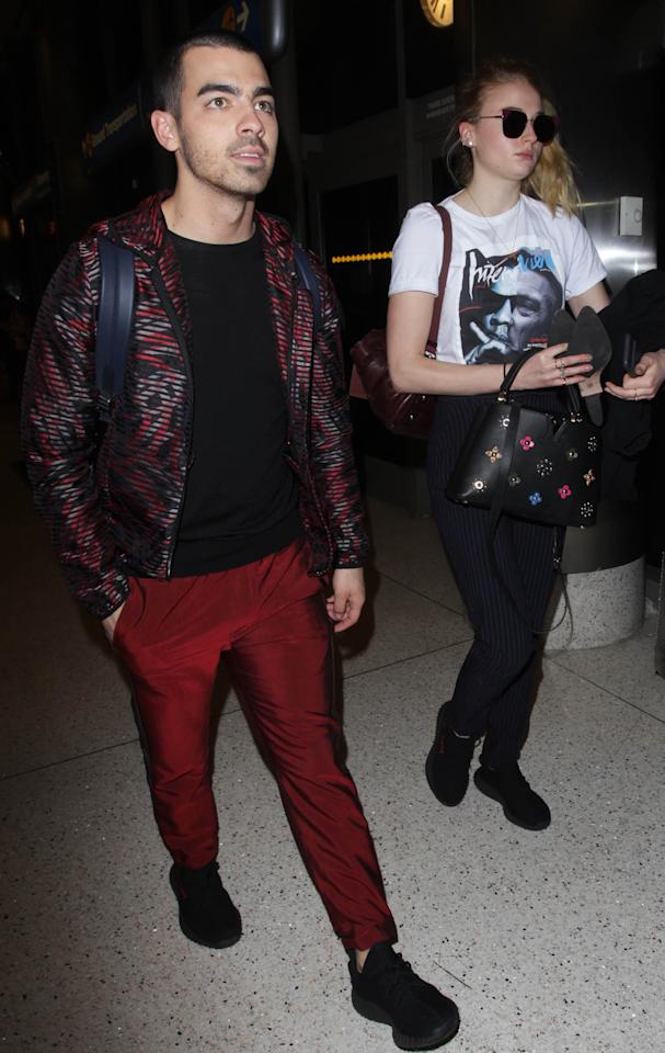 <p>At LAX, Turner and Jonas looked ready for a long flight, Turner holding her heels and wearing black sneakers, pinstripe pants, and a graphic tee, and Jonas in red shiny pants, a black tee, and red and black patterned zip-up. </p>