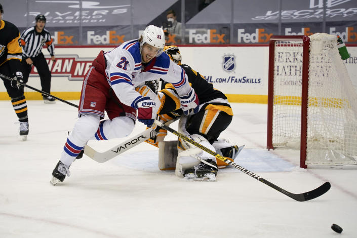 New York Rangers' Brett Howden (21) tries to get to the puck in front of Pittsburgh Penguins goaltender Casey DeSmith (1) during the second period of an NHL hockey game, Sunday, March 7, 2021, in Pittsburgh. (AP Photo/Keith Srakocic)